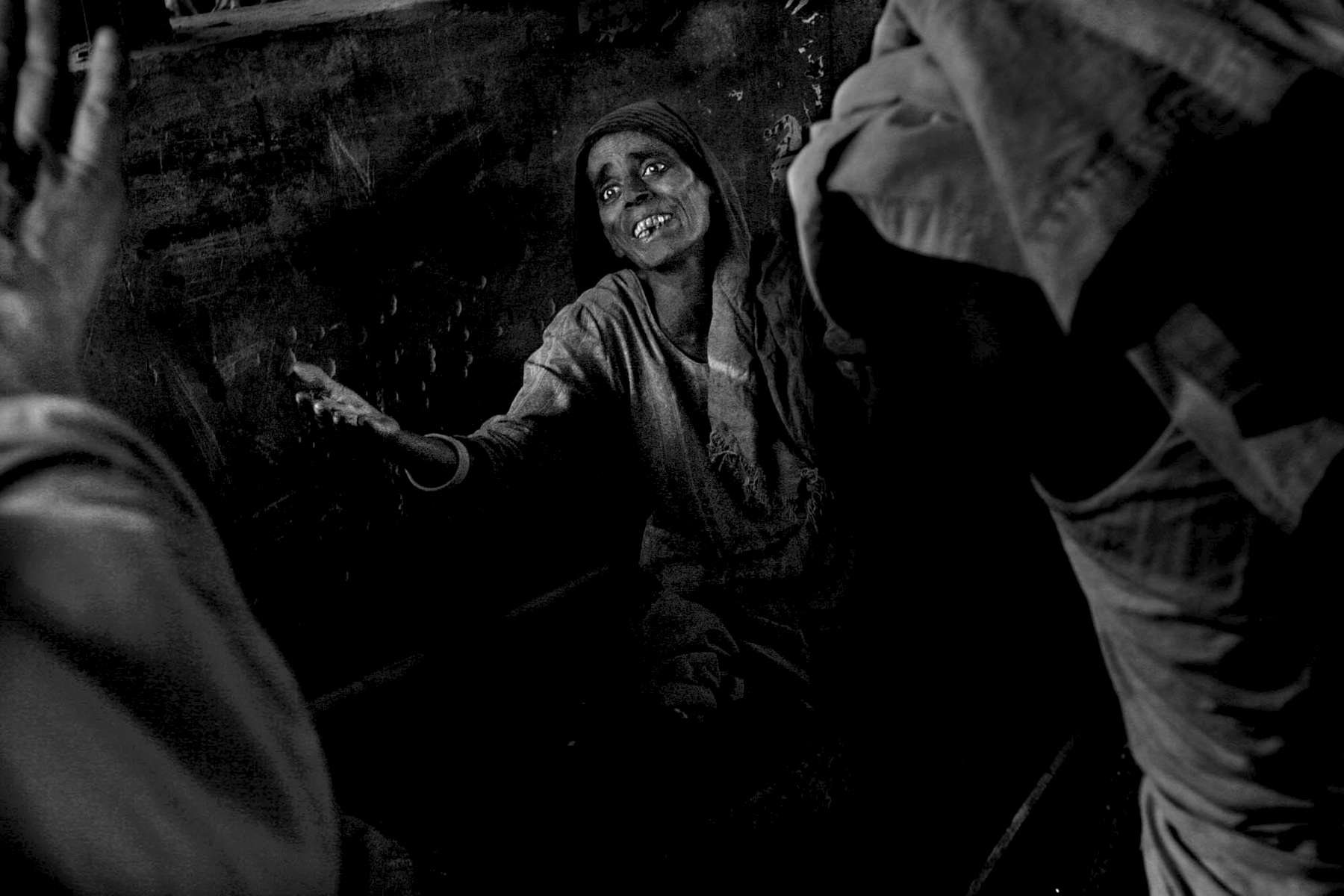 A woman cries out for assistance from a passerby under a bridge in New Delhi. Thousands of people live in blinding povertyi n the capital city.
