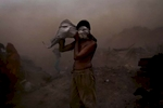 A man shields his face during a sandstorm in New Delhi.