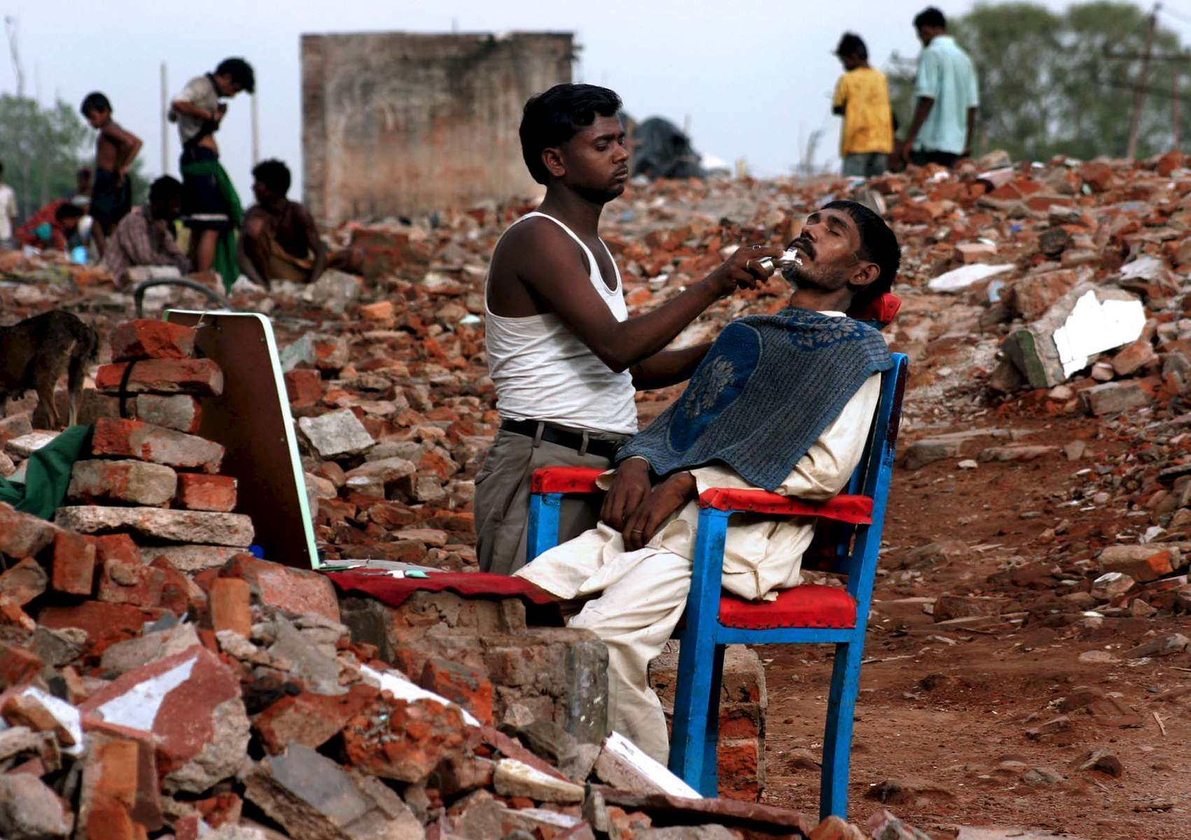 A barber shaves a customer at a roadside stand in New Delhi in the Yamuna Pushta region.