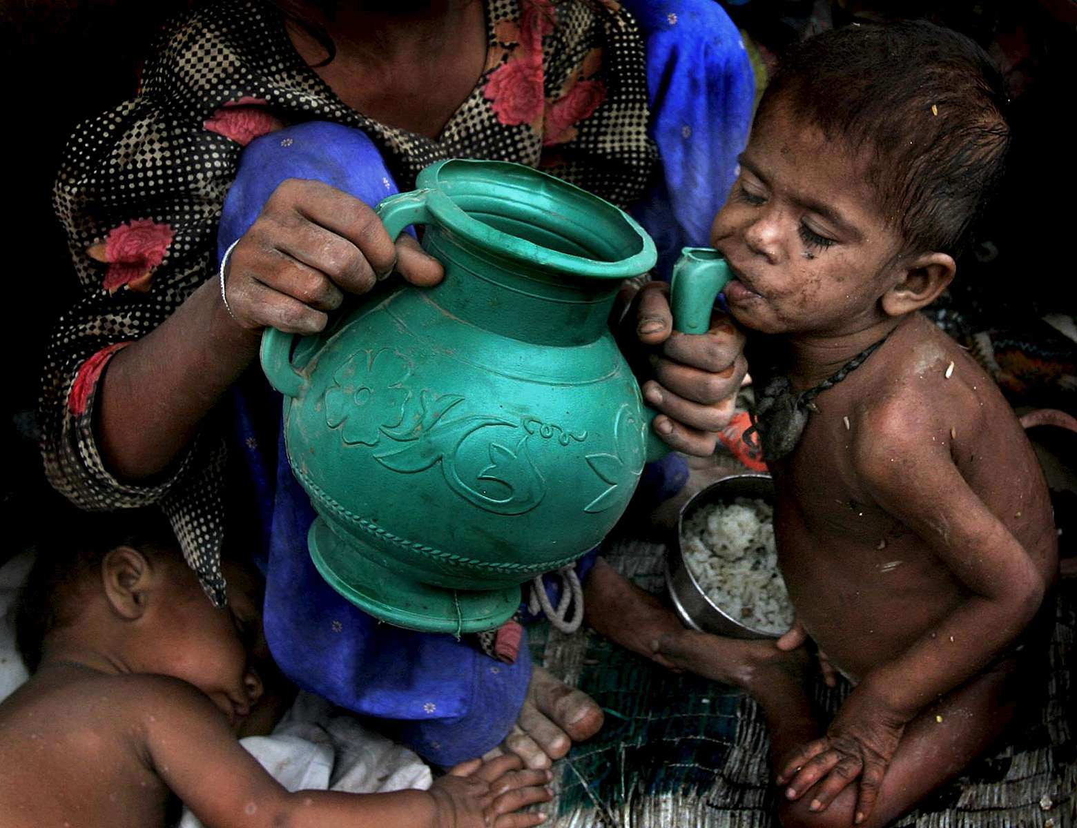 A girl gives her younger sibling a drink of water in a slum-region of New Delhi.