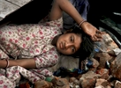 A child lays on a bed of bricks which also serves as her bed in the aftermath of the destruction of her home in the Yamina Pushta region of New Delhi.