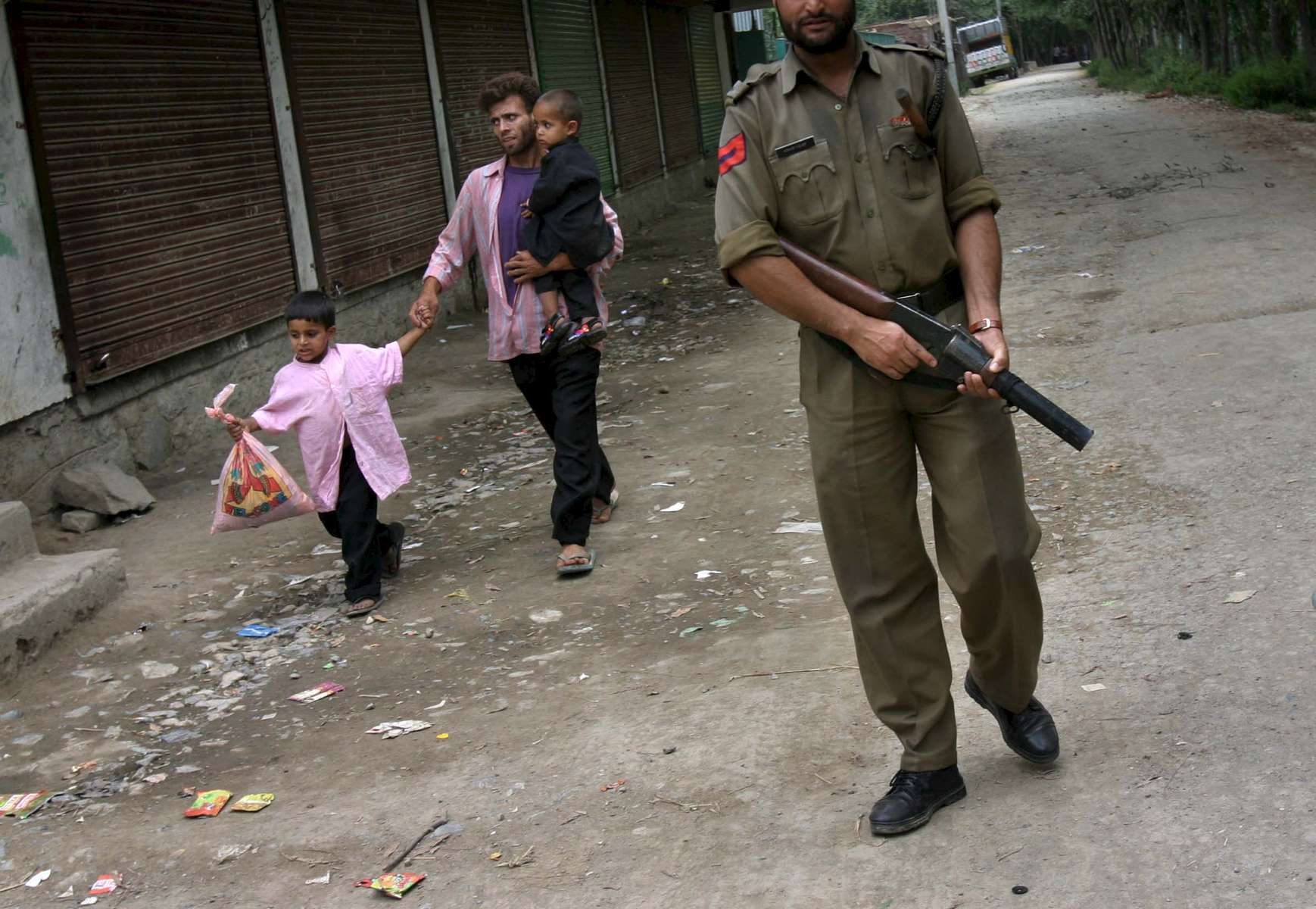 A Kashmiri family skirts by an Indian military personnel who was on patrol during the aftermath of a protest. Scores of villagers outside of Srinagar were protesting the killing of a militant.
