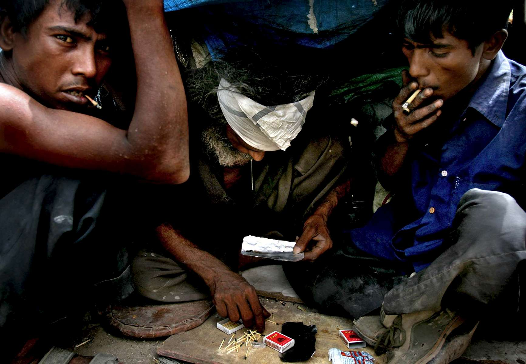Alburt, center, smokes {quote}Smack{quote} with the help of his friend, Abdul Qadir, left, while Salim keeps a watchful eye out. Many drug addicts use {quote}Smack,{quote} or smokable heroin, to cope with the harsh reality of life in Yamuna Pushta.
