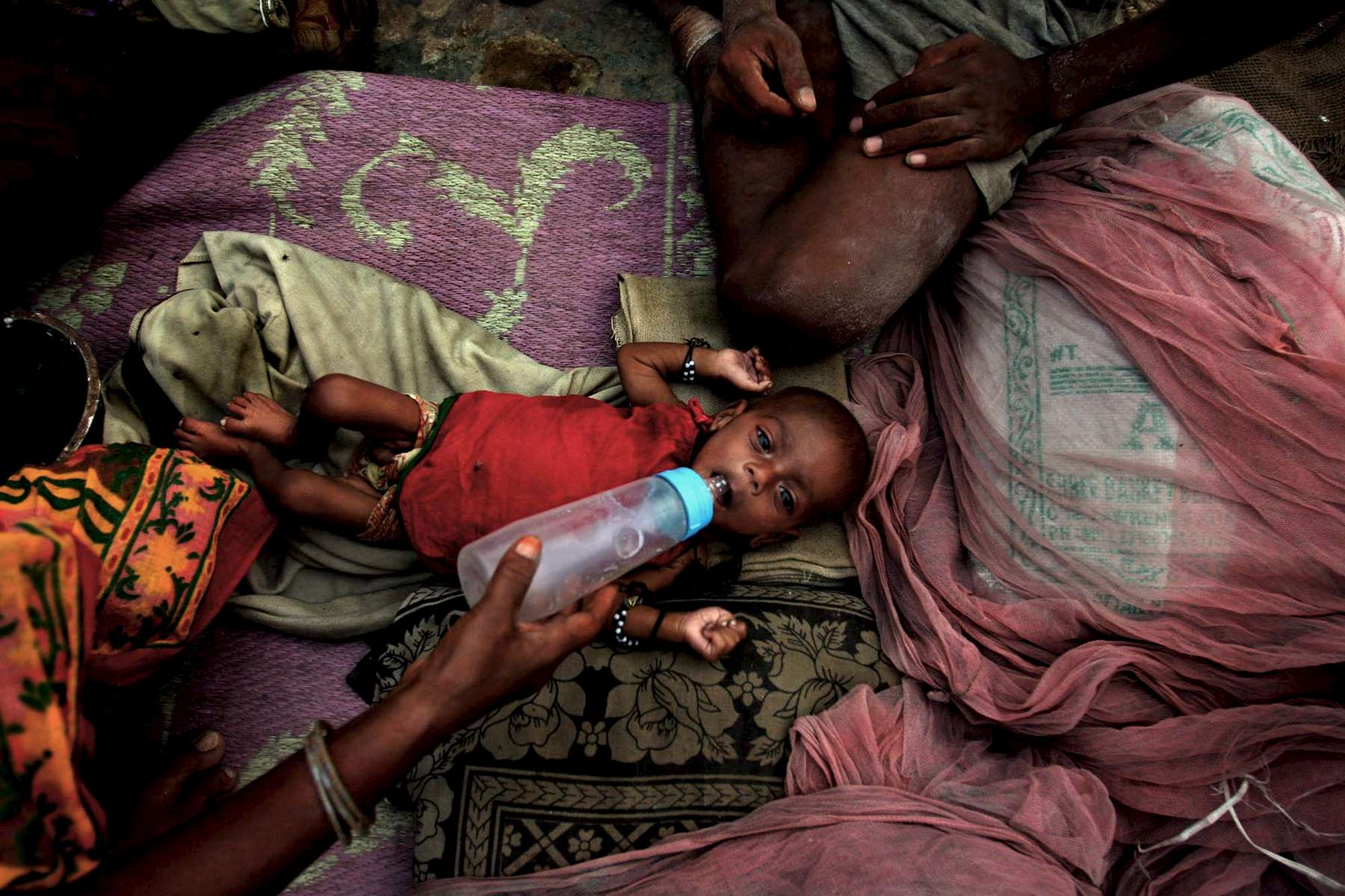 A mother feeds her newborn baby in Yamuna Pushta a diluted milk solution one afternoon. Babies and young children are often undernourished due to the lack of access to proper nutrition in the community.
