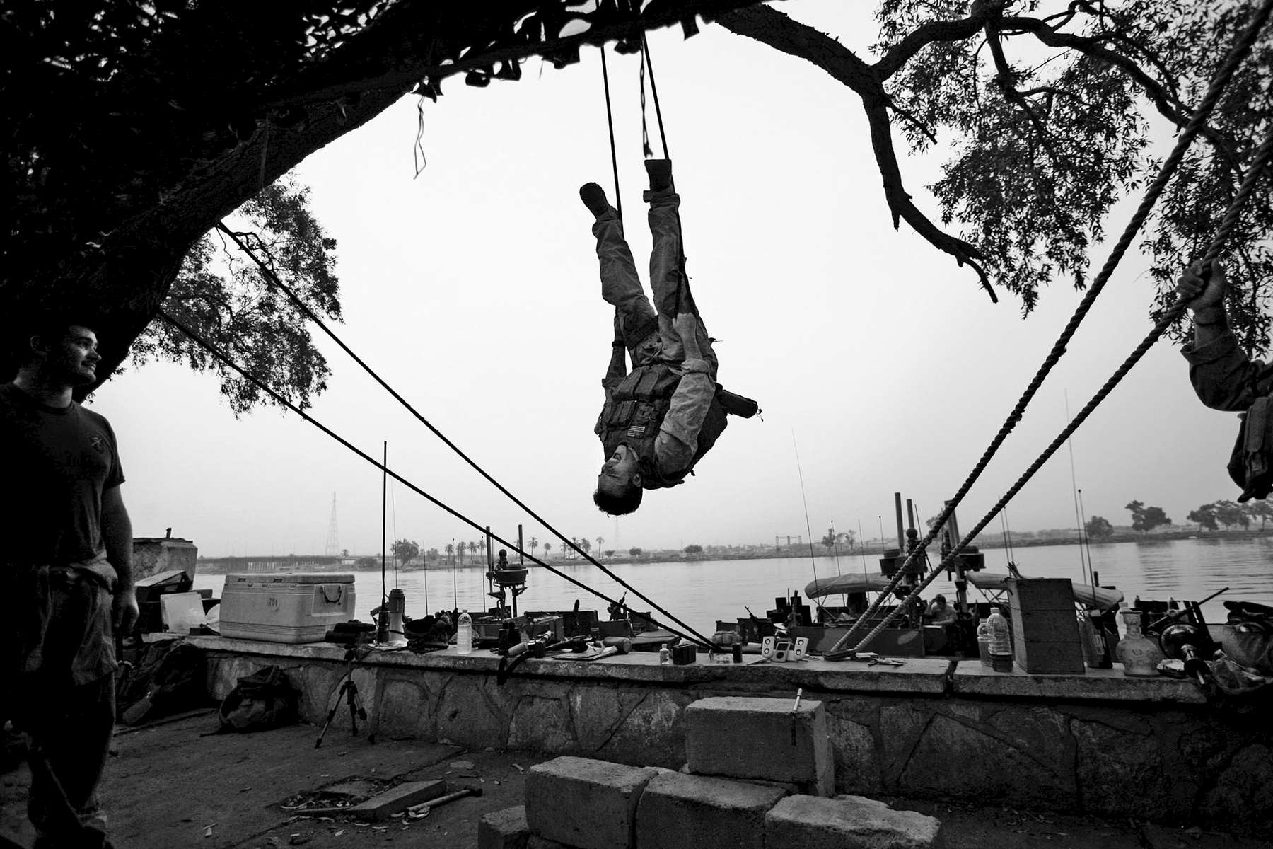 There's more time to fill these days as the number of missions and personnel decrease - here Sid Pollock, 20, of Norfolk, kills time by trying to see if he can hold himself upside down on a rope. Pollock is a seaman with Navy's Riverine Squadron One.