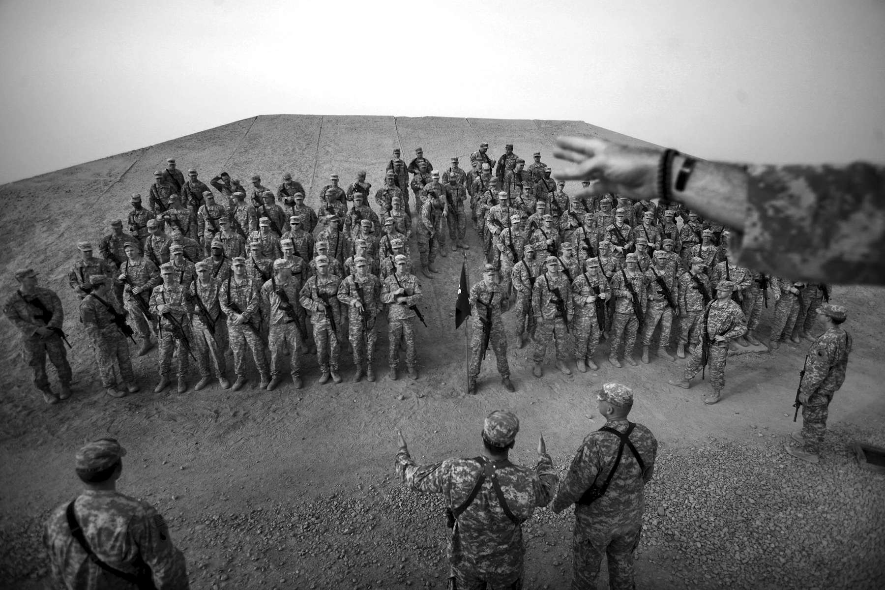 Soldiers from Virginian National Guard's Bravo Company line up for a picture at Camp Adder in Iraq. They are posing for one of their last group pictures before returning home. The place they are posing is an old bunker used during the Saddam Hussein reign.