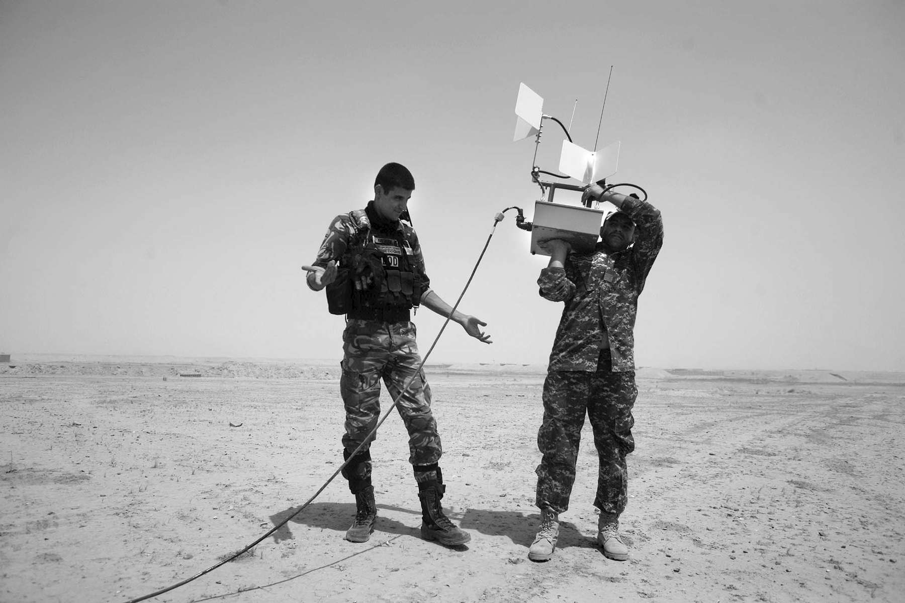 Nawfal Hotaf, left, wonders the best way to hold the antenna to operate the robot while working with Ahmad Shalal, right as they work with the Navy's Explosive Ordnance Disposal Mobile Unit 2 in Iraq at COB Speicher during a training exercise. Both men are with the Iraqi Police and are working with explosives removal in Iraq.