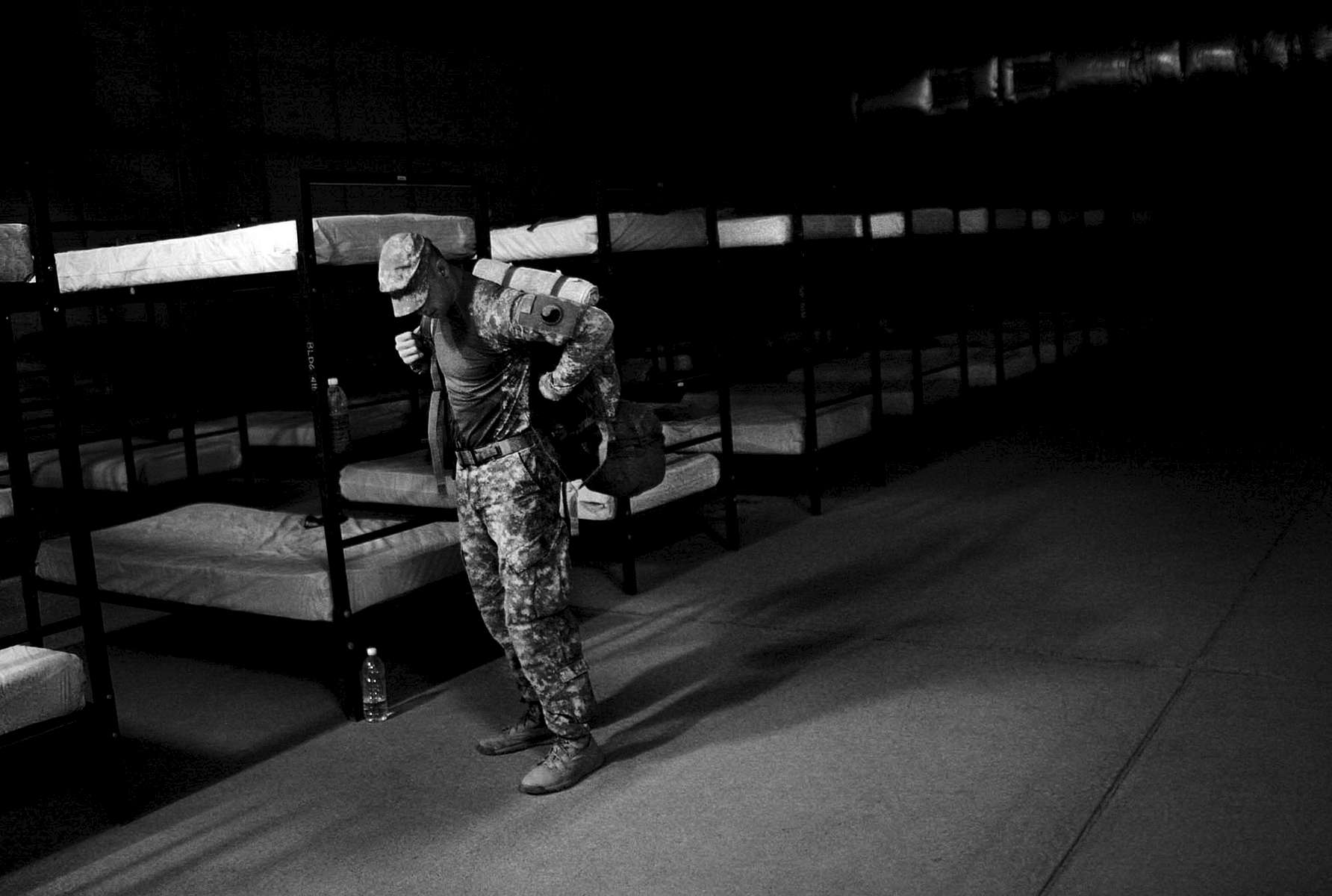 Lines of open sleeping areas string into the dark as Cpl. Joshua Marston, 23, of Culpeper, loads up at Camp Taji in Iraq. He was one of the last to leave the sleeping area on the last mission of their convoy group. Marston works as a gunner in his vehicle. Marston is with the Virginia National Guard.