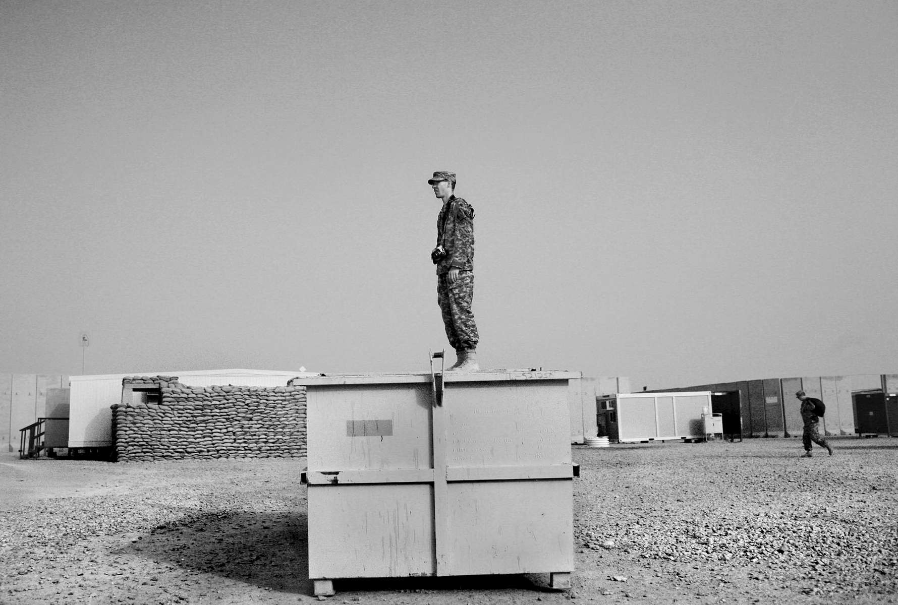 A soldier with the Virginia National Guard stands on top of a garbage container to try to get a better photograph at Camp Adder in Iraq.