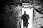 A soldier heads out under an exit sign at Camp Adder. He'll be one of the tens of thousands of soldiers that will be returning home soon as part of the draw down of American forces in Iraq.