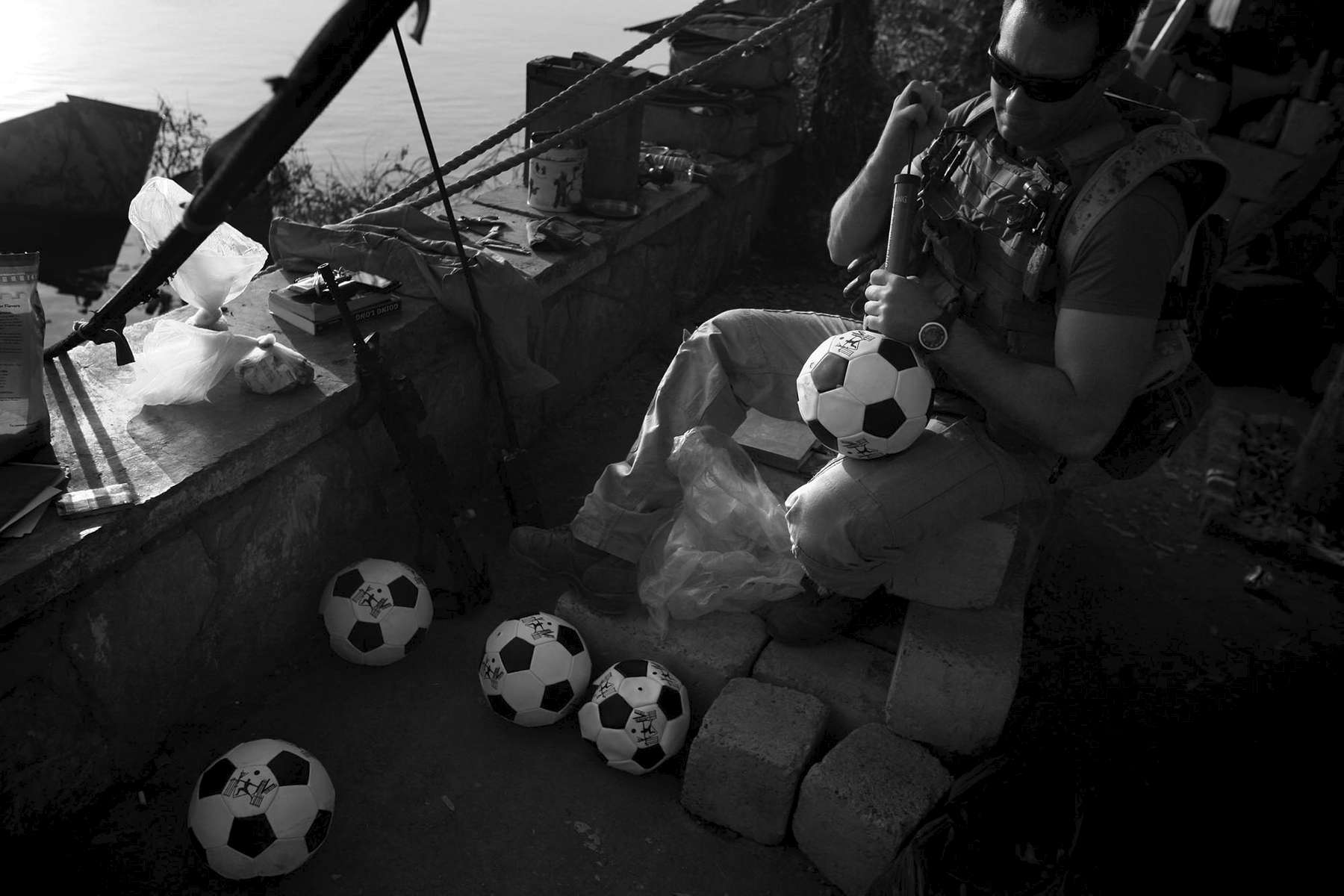 Seaman Chris Welch, 27, pumps up soccer balls which will later be given while the Navy's Riverines are out on patrol in Iraq. The unit routinely gives out soccer balls as part of the {quote}hearts and minds{quote} campaign. As the war winds down, soliders spend more time with such transitional acts. Welch is from Norfolk and is part of the Navy's Riverine Squadron One.