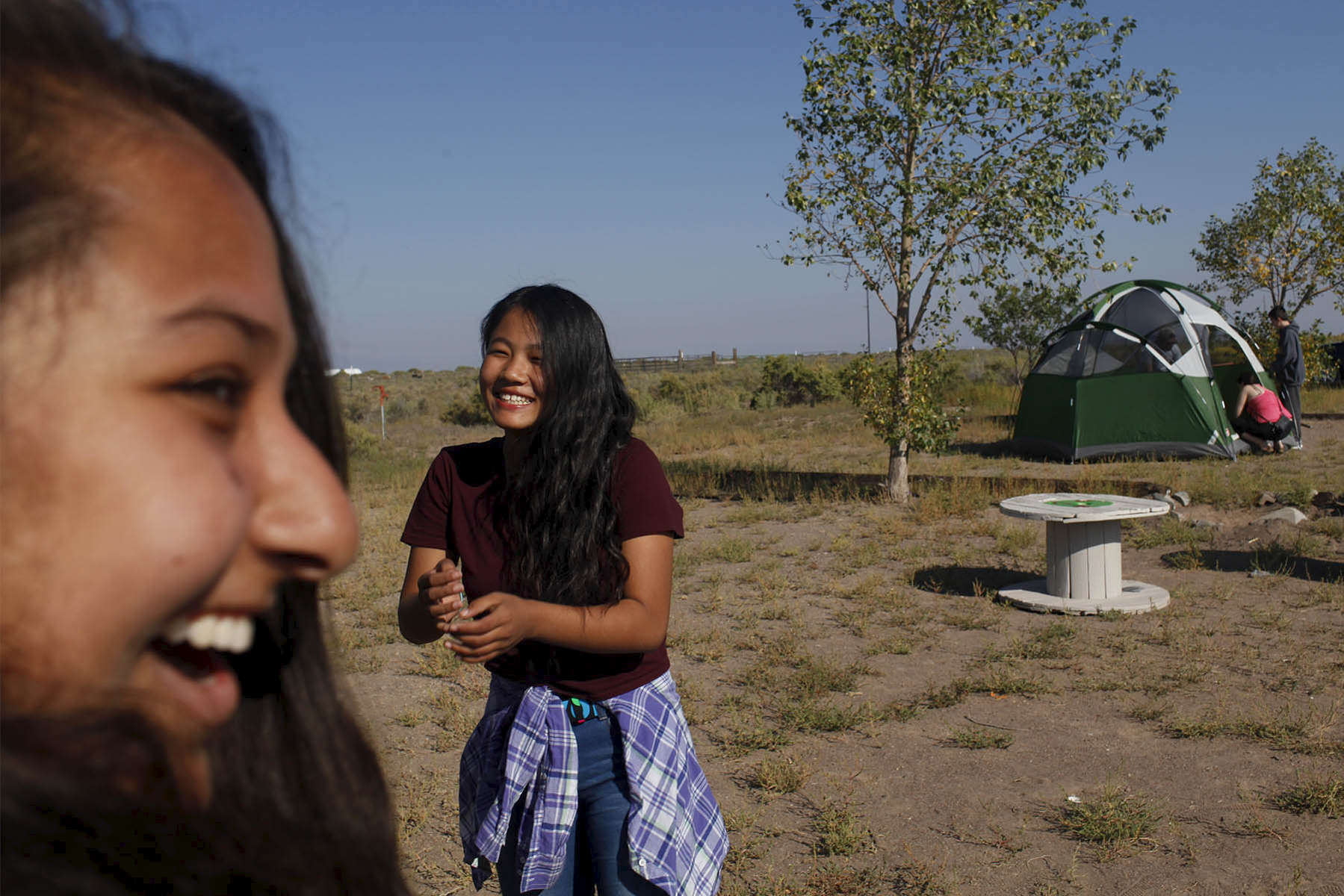 Nirshika Neopany, 14, left and Dechen Drukpa, 14, right, laugh together before making breakfast at their campsite in Hooper, Colo. on Sept. 3, 2017.