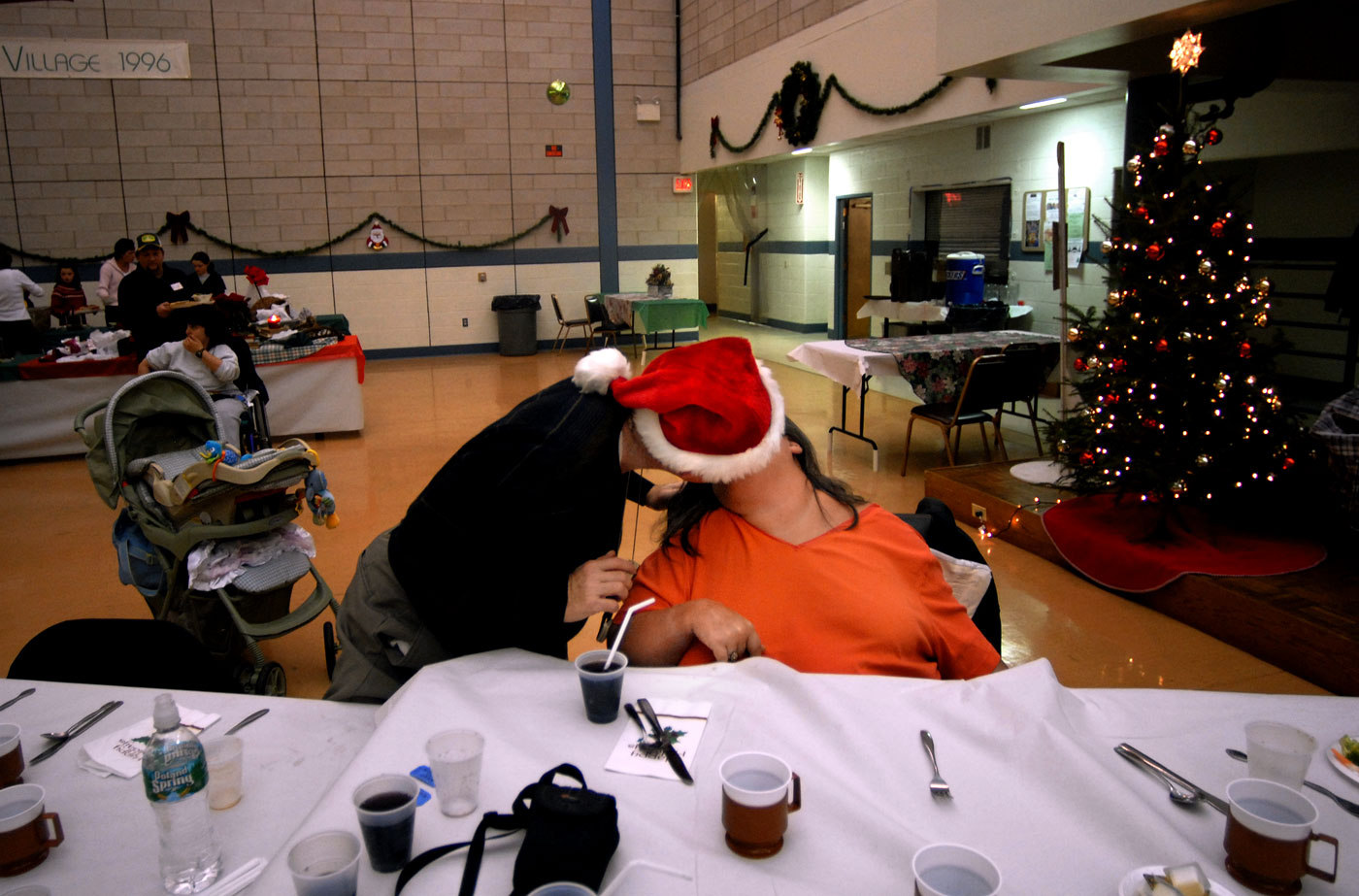 Tom leans over to give Theresa a big smooch during a village-wide Christmas dinner celebration in New Horizon's Great Hall.