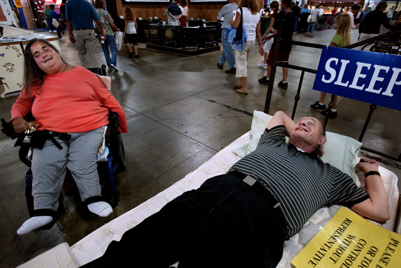 "Theresa Rogenski chuckles at Tom while he kicks back on a bed for sale at The Big E this past fall after a long day walking behind Theresa. At age 64, it can be exhausting for Tom to be on his feet for hours at a time, but as long as he's behind Theresa, he doesn't seem to mind. ""Some people make a big deal about the age difference between us,"" says Tom. ""But we don't give two hoots about age. Age is just a number."""