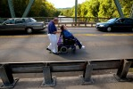 "Tom and Theresa Rogenski cross the bridge on Main Street over the Farmington River. The two sometimes opt to travel in the roadway instead of the sidewalks due to the breaks in the sidewalk which can be problematic to negotiate in Theresa's wheelchair. The couple was traveling on this day to Unionville center to tend to some shopping and banking. The scene looks precarious, but with Theresa watching for traffic, they make it safely. ""If you say we can't make it, we won't,"" says Tom. ""If you say we can, we will. Not without its hardships, but we will."""