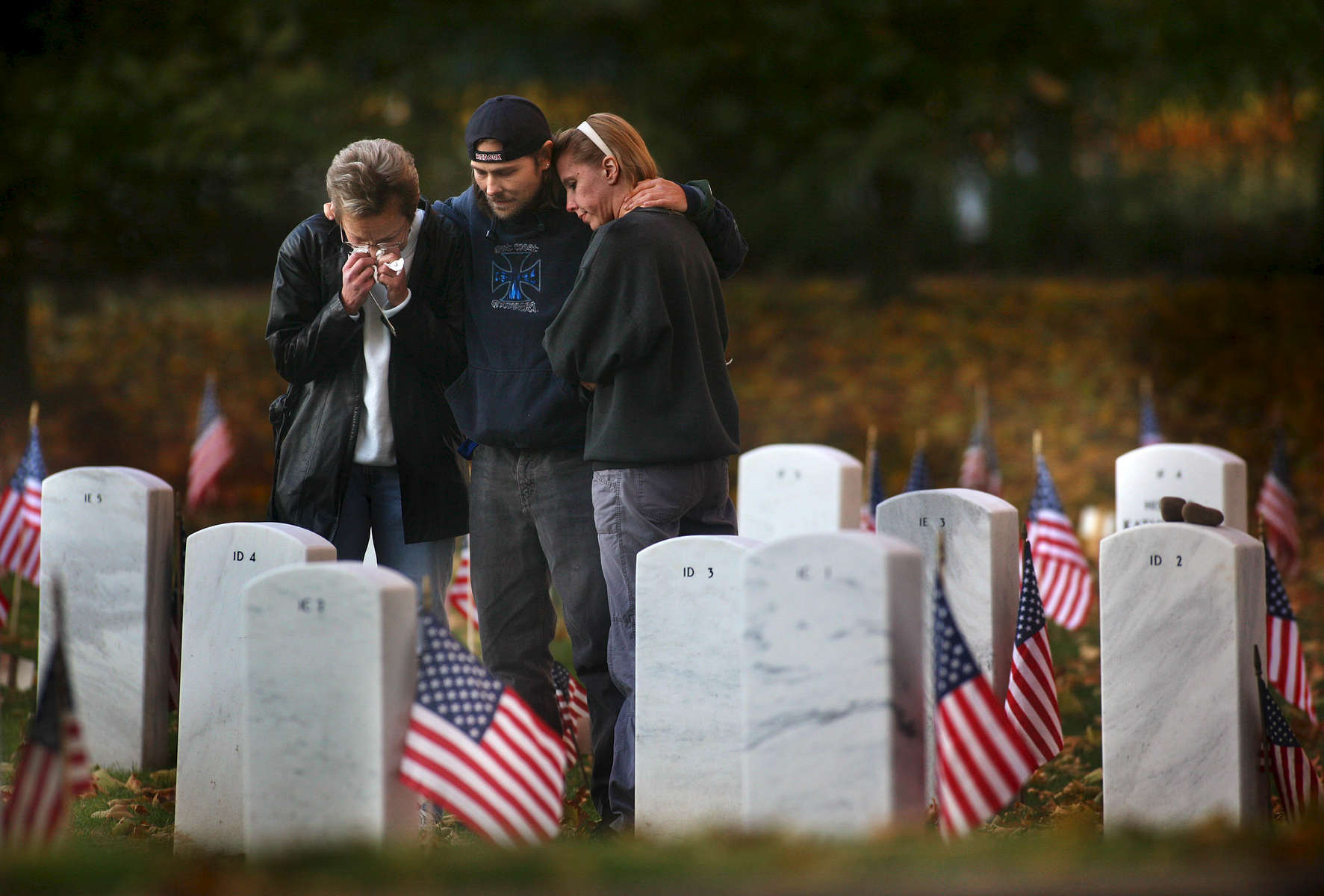 (l-r) Judith Grundwalski, Richard Grundwalski and Denise Prokop visit the grave of Richard Grundwalski , Sr. at the State Veterans' Cemetery in Middletown, Connecticut. Richard served in Vietnam in the Army and completed a total of six years in the service - he died last year due to complications from various illnesses. He was married to Judith and is the father of Richard (pictured here) who said that he came to tell his father the news that he recently got engaged to Denise.