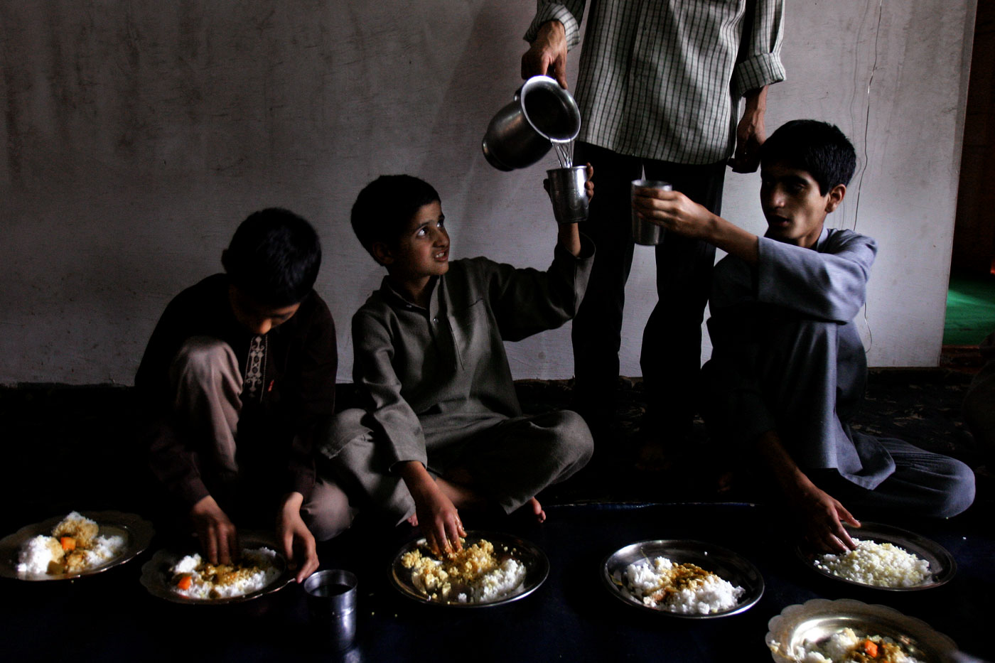 (l-r) Mozam Iqbal, Nasir-Ul-Islam, and Waqar Ahmad have lunch at the orphanage.The children receive three nutritious meals each day, meals they may not otherwise receive if they were living on the streets.
