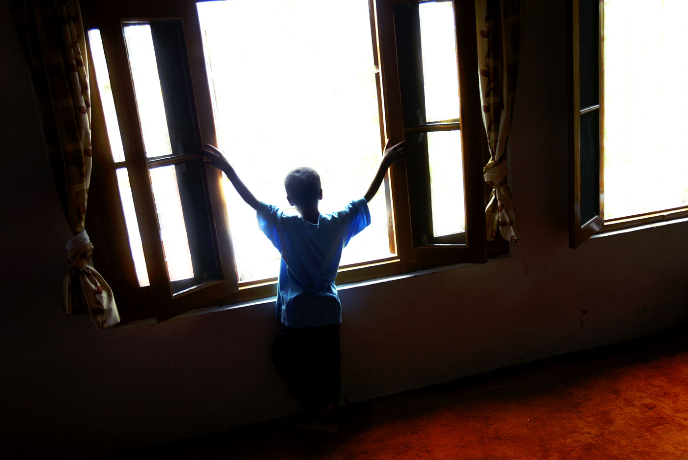 Imtiyaz Ahmad looks out the window from his bedroom. He, like so many other orphans, face an uncertain future.