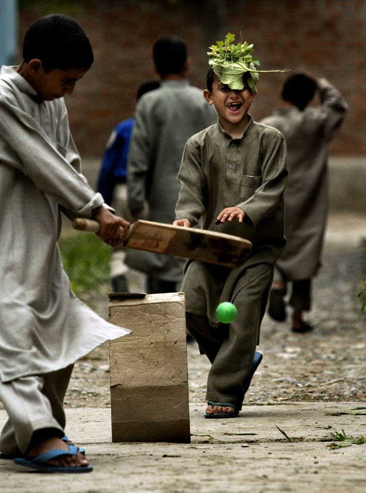Basit Bashir, left, and Tahir Javid play a make-shift cricket match outside the orphanage.
