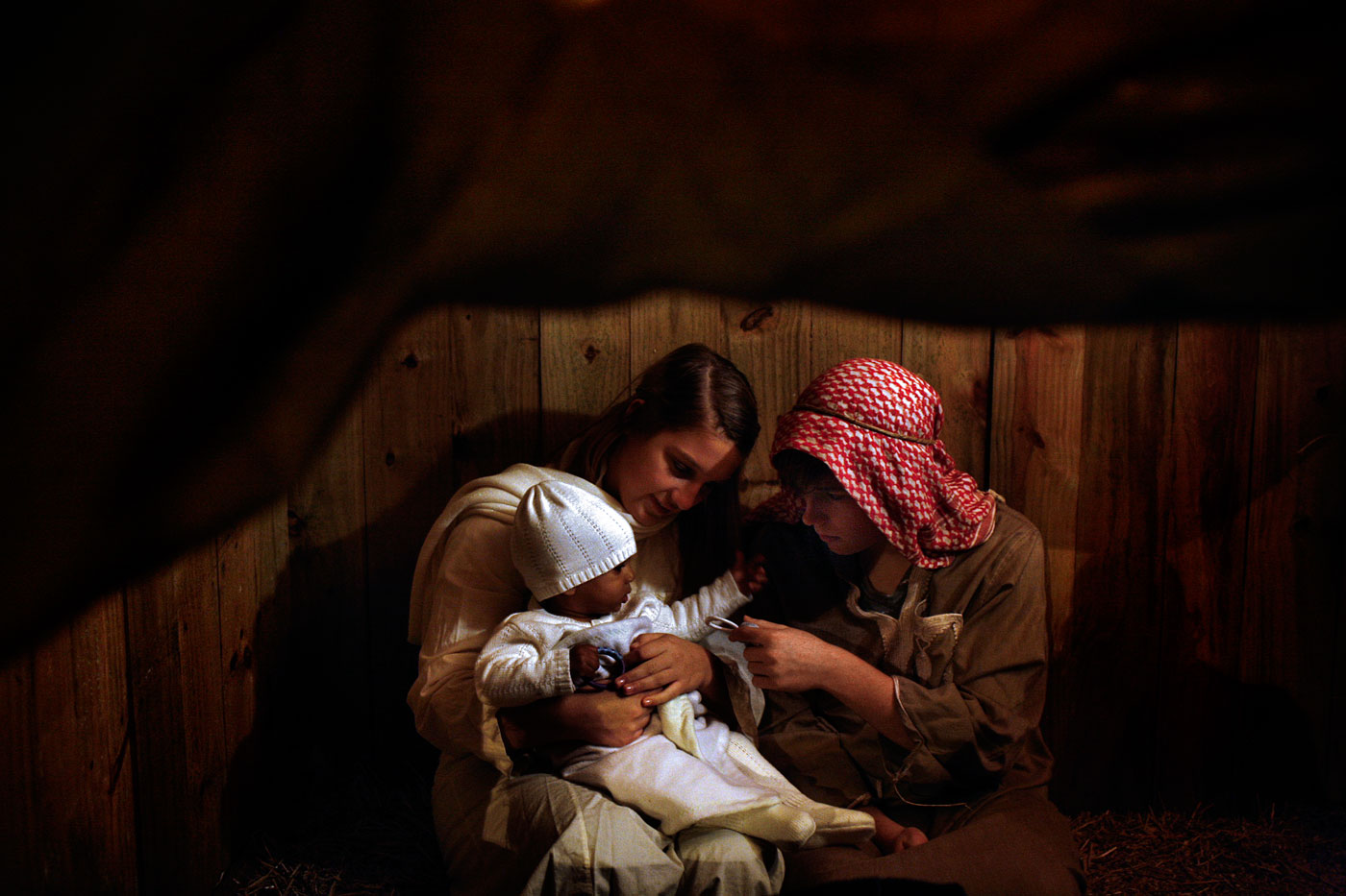 "Just inside a wooden shack, next to the plastic playground, Leah Dickerson, 15, cuddles Jasmine Reyes. Leah's brother, Zach Dickerson, 17, picks up a pacifier and hands it to Jasmine's little sprouts of fingers. The siblings play Mary and Joseph - and Jasmine, an African-American girl, plays Jesus Christ - during the Bethlehem Walk at King's Grant Presbyterian Church in Virginia Beach. It's an unconventional approach to the timeless Christian tradition, but one that draws nothing but admiration by those in attendance.""I think it's important to share our faith with other people,"" said Zack. ""Even though it's like a walk-through play, it may change someone's faith in what Christmas really is about. The bible commands us to share our faith with other people and to spread the good news of the gospel, of Jesus."" ""It's an honorable experience,"" said Leah. ""You have this feeling that people care for you and they want to see baby Jesus and his mother."""
