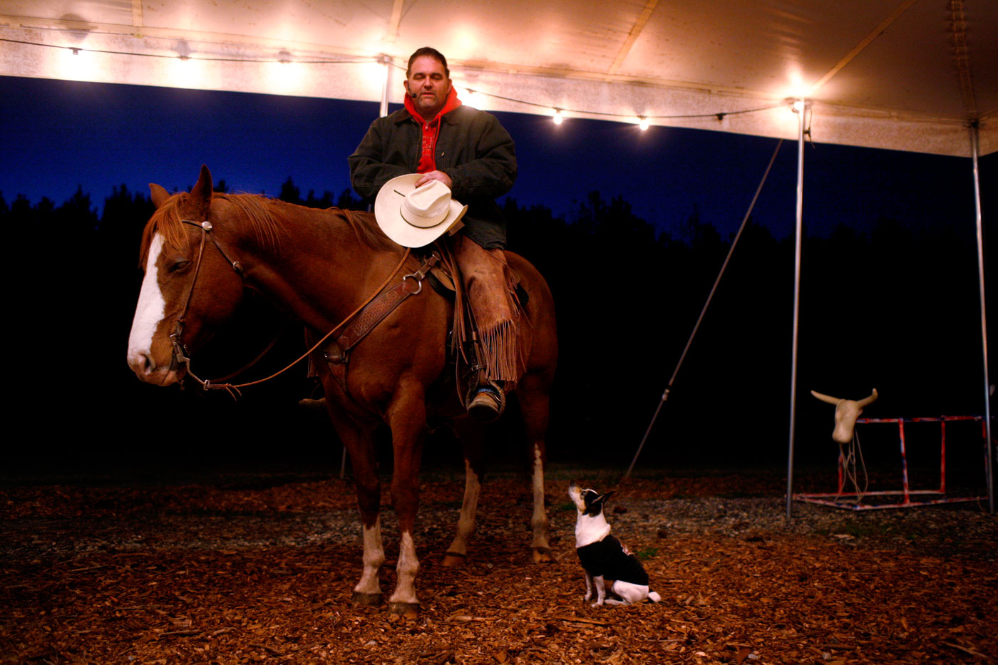 """Tim Kirkpatrick bows his head and slips off his cowboy hat. He begins to pray.   Below him, a small terrier mix named Sheriff Woody wags his tail and scampers in the dirt. Kirkpatrick, 40, is a part-time pastor of the Hickory Ridge Cowboy Church.   """"We started it so we could reach people with an outdoors mind,"""" he explains. """"There's a lot of farmers, horse people and animal people around here. This is the avenue that we use to reach them.""""   Members meet Saturday nights in a large tent set up on the grounds of Hickory Ridge Community Church in Chesapeake.   Kirkpatrick says he caters to Christians who aren't comfortable with traditional services. He recalls one uneasy congregant who told him, """"If I can come with manure on my boots, wear my blue jeans and if I don't have to put my teeth in, then I'll come."""" """"It's God leading it, I'm just along for the ride, said Kirkpatrick. """"These are my people, and it's a great way to reach them for Christ."""""""