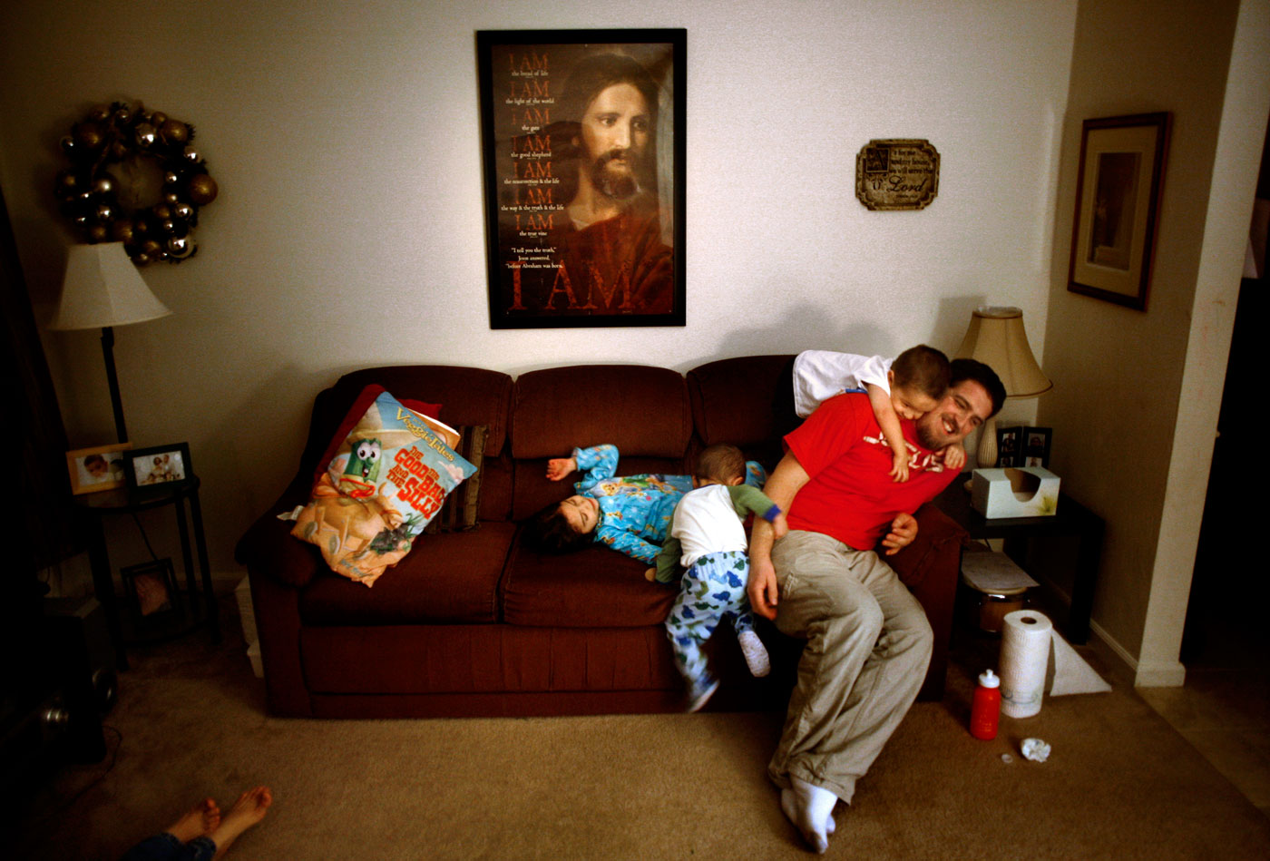 "Jacob Kendrick, 2, pounces in his padded dinosaur pajamas onto his father, Mike Kendrick, as his other son, Dylan, 3, drapes over his back. His daughter Lily, 5, laughs.It's all under the watchful eye of a Jesus Christ poster that proclaims {quote}I Am.{quote}The poster hangs as a centerpiece of their living room.  ""It's important for our kids to constantly see that he is our solid rock,"" said Mike. ""It's like having a picture of a loved one in your office.""It's a prelude to a nightly worship time for the Virginia Beach family. On this evening, the kids are wound up and needed to bounce out some energy before prayer.""I think it's what holds us together, having the altar time,"" said Nereida, Mike's wife.  ""It's important  for them to know that we're there for them, and that Christ is there for them as well."""