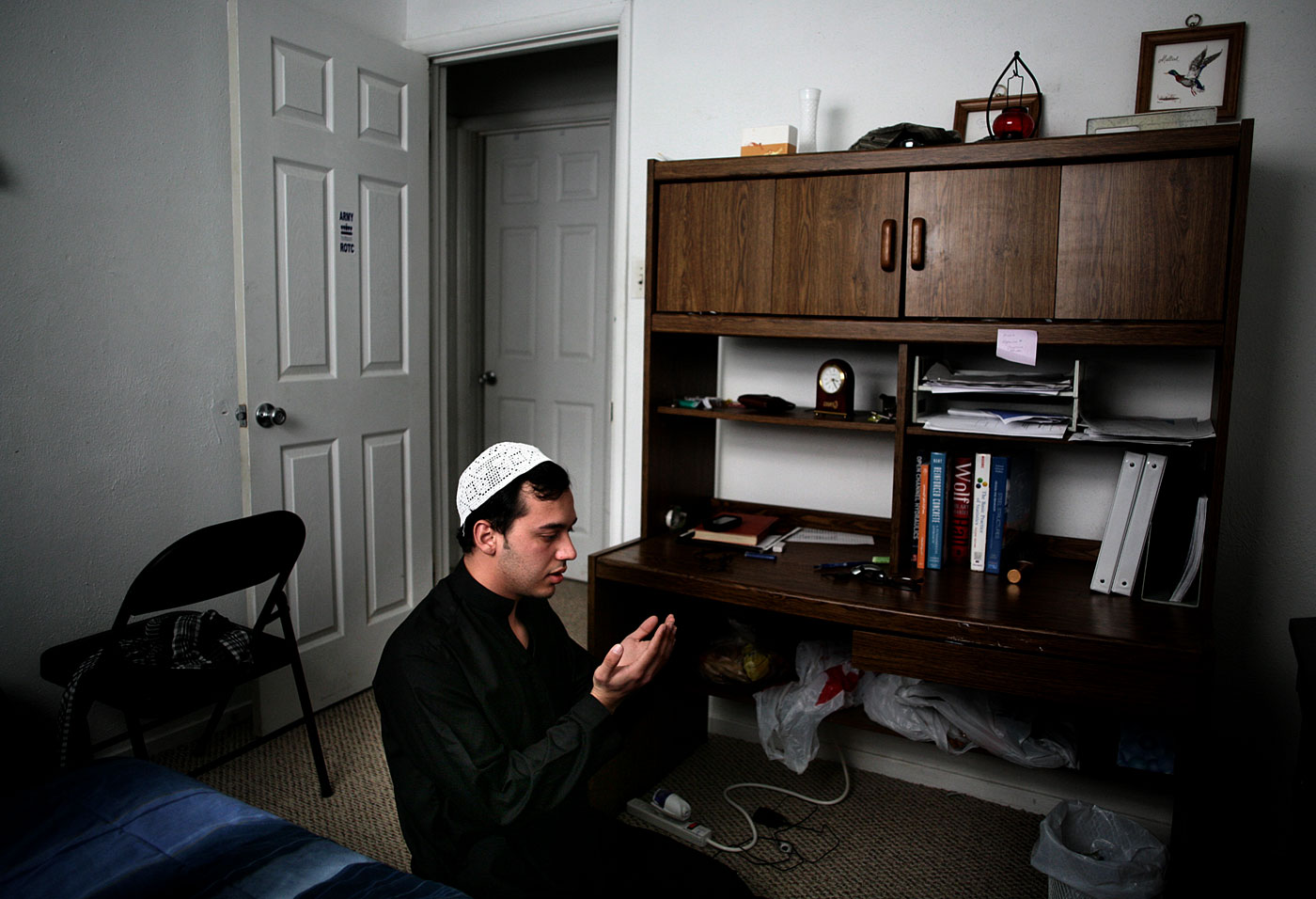 "Sulaiman Banwal, 24,  opens the door to his bedroom and slips on his white prayer cap. He unfurls a prayer rug and bends bedside to the floor. He's wearing in a black perahan tunban, the traditional garb of Afghan men. He faces a wall draped with inspirational Islamic sayings.The silence is broken by the rustle of his clothing as he bows prostrate. Somewhere in the distance is Mecca.""Praying is a responsibility for every Muslim,"" said Banwal, who, despite living 7,000 miles from home, still prays five times a day. He is a Fulbright Scholar from Kabul, Afghanistan. He attends Old Dominion University and is earning a master's degree in civil engineering.He believes that praying to Allah helps him with his daily life. ""In our religion you never lose hope, because losing hope means you're not believing in God anymore.{quote}{quote}You feel like home, you don't feel alone,"" he said of the call to prayer. ""You're never alone, because God is with you."""