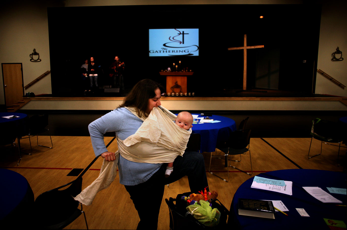 "Stephanie Goetsch clamps the cloth between her teeth and curls her newborn tight.A scattering of circular tables dots the gym floor and four basketball goals frame the sidelines. It's almost time for church.""We started the church in September and he (Luke) was born in October,"" Goetsch says. ""He's the first lifetime member. In fact, he's automatically a member because we are.""The 26-year-old attends The Gathering United Methodist Church, a burgeoning congregation that meets in the gym of Courthouse Community United Methodist Church in Virginia Beach. It holds two services a week and targets young adults.{quote}We like it because it's more family oriented,"" Goetsch says. ""Because it's a new church, we have more input into how things are."""