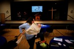 """Stephanie Goetsch clamps the cloth between her teeth and curls her newborn tight.A scattering of circular tables dots the gym floor and four basketball goals frame the sidelines. It's almost time for church.""""We started the church in September and he (Luke) was born in October,"""" Goetsch says. """"He's the first lifetime member. In fact, he's automatically a member because we are.""""The 26-year-old attends The Gathering United Methodist Church, a burgeoning congregation that meets in the gym of Courthouse Community United Methodist Church in Virginia Beach. It holds two services a week and targets young adults.{quote}We like it because it's more family oriented,"""" Goetsch says. """"Because it's a new church, we have more input into how things are."""""""