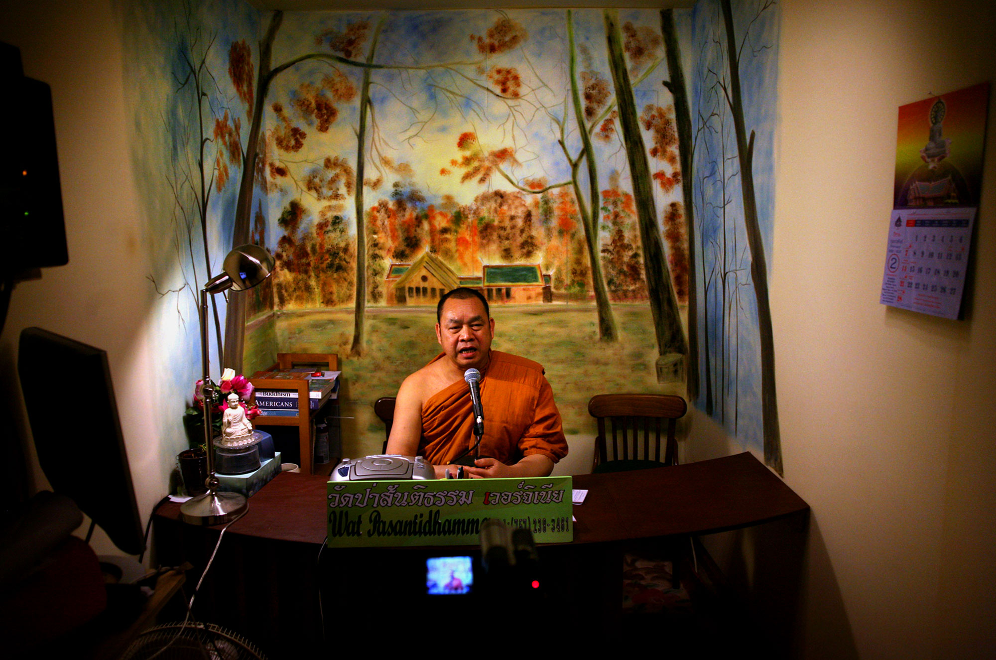 "Udom Budsriphoom steps behind the desk and takes his seat in front of a bucolic woodland scene. He's wrapped in saffron orange, save his right shoulder, which is bare.He peers over one of the monitors and takes a breath. A red light indicates that the DV recorder is on. The sound-proof room sucks up his words as they spill over the silver microphone.Welcome to Dhamma Talk, a nightly installment of the teachings of Buddha at Wat Pasantidhamma in Carrollton, Va. Each night for about an hour the head monk records teachings of the Buddha to be posted on the temple's Web site. ""It's a way for us to tell the teachings of the Buddha."" says Budsriphoom, the head monk and a native of Thailand. ""It's also a chance for us to give spiritual advice to people.""""Sometimes you feel lonely,"" Budsriphoom says. ""Sometimes we feel shy – you don't feel comfortable when you talk alone.""You try to imagine many people listening to you around the world."""