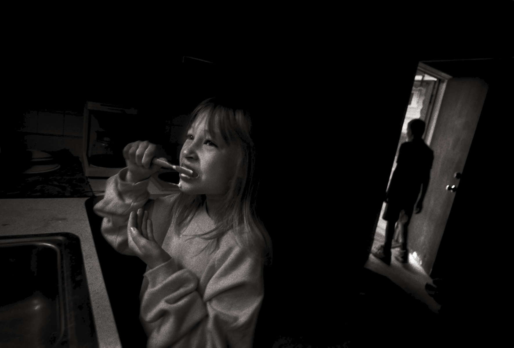 Amanda Rose brushes her teeth one morning in the kitchen sink while Clifford Rose is framed in the doorway.
