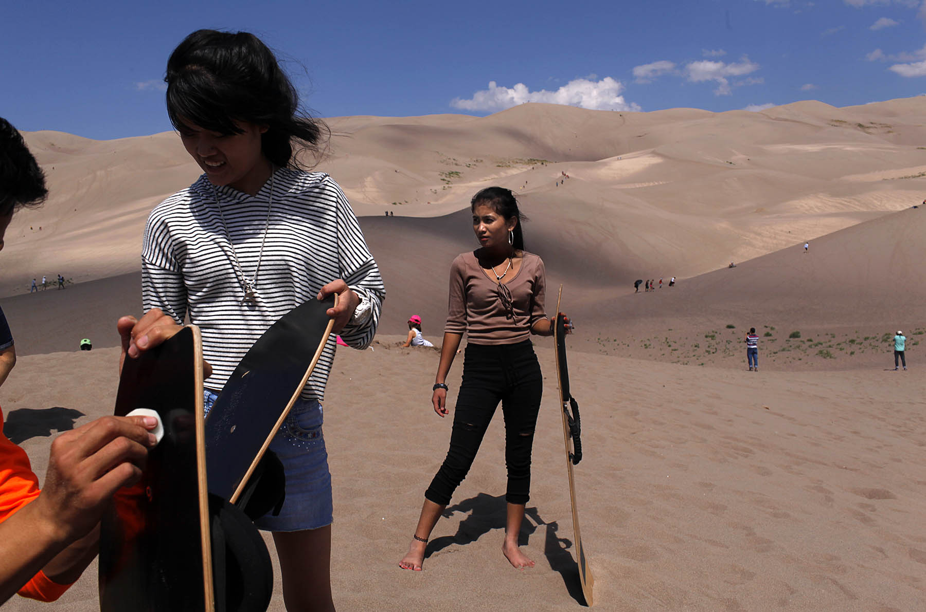 Puja Rai, 14, left and Sapana Gurung, 14, right, prepare to ride down some of the dunes on Sept. 2, 2017. The crew spent a large part of the day at the Great Sand Dunes National Park and Preserve.