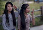 Sapana Gurung, 14, right, checks to make sure she makes the correct Boy Scout of America hand sign on Sept. 2, 2017 during one of their campouts. At left is Puja Rai, 14.