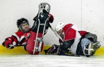 Connecticut Sled Hockey player Tyler Konvent, right, crashes into Ottawa Barbarians Alain Bazinet during their opening game of the tournament in Ottawa. The first game was the only game that Connecticut lost.