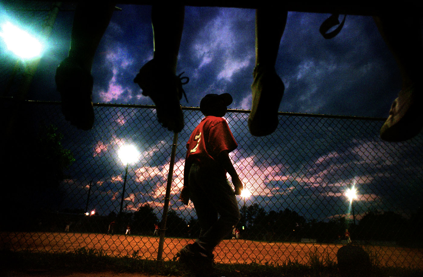Korea Price paces along his dugout while waiting for his turn to bat during one of his team's Little League baseball games in Durham, North Carolina.