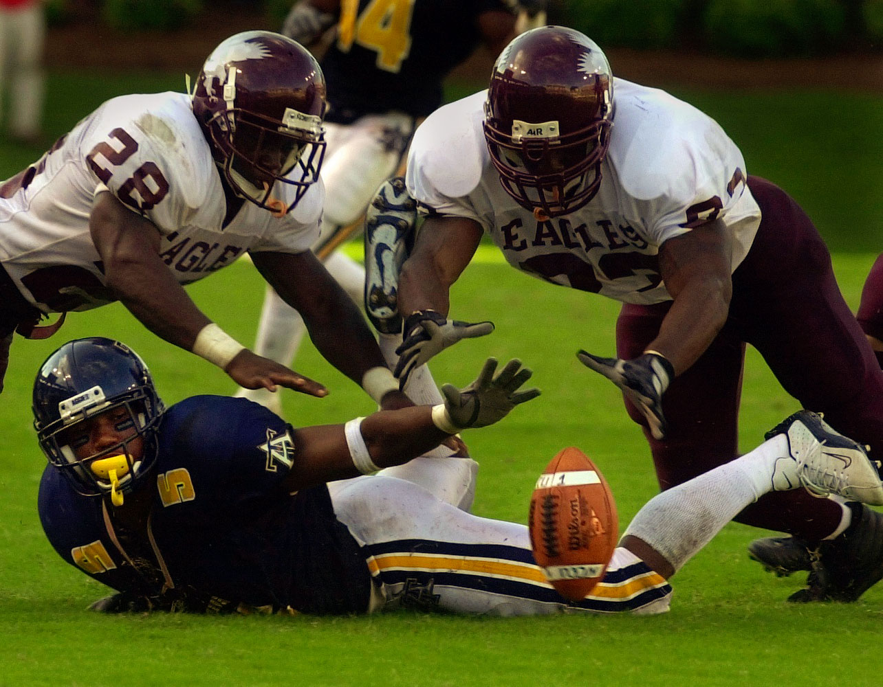 North Carolina Central University football players DeLeon Raynor, (28) left, and Jamar Neely dive for a loose ball during their victory over N.C. A &T during the Aggie-Eagle Classic at Carter-Finley Stadium in Raleigh. NCCU won 33-30. At bottom is Aggies' Douglas Brown.