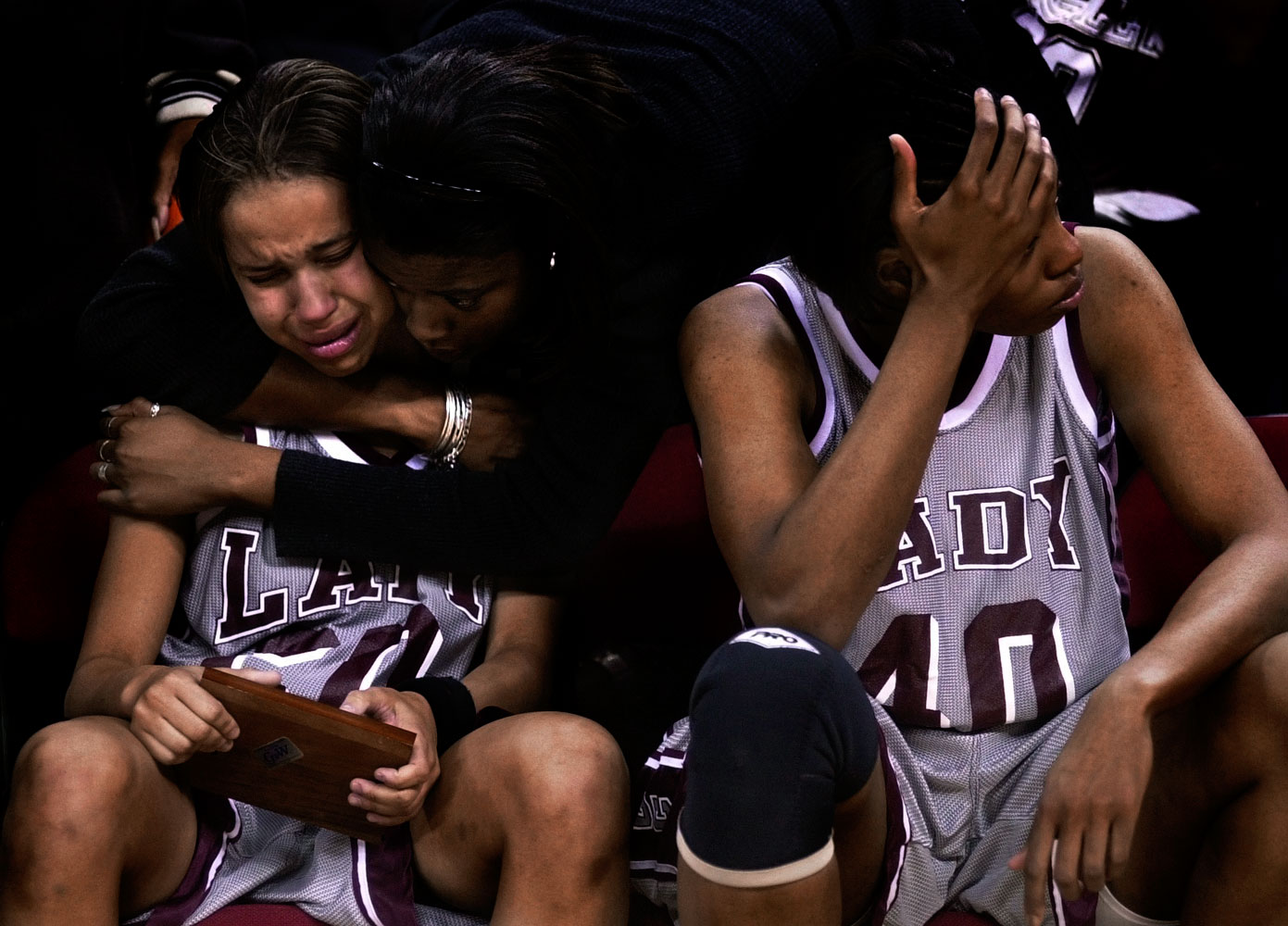 Former NCCU basketball player Fatima Bah consoles Tiona Beatty (20) after their loss in the championship game of the CIAA tournament in Raleigh, N.C. At right is Connie Murdoch (40).