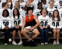 Dressed as a cheerleader, David Miller {quote}adjusts{quote} himself before a school photographer takes a team portrait for their annual {quote}Powderpuff{quote} football game. The Powderpuff game is where the girls dress as football players and participate in the game, while the boys dress as cheerleaders and root them on.