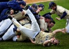 Trinity College's Kent Graham (6) rolls off a pile of teammates as they erupt with excitement after they won the championship game in the NCAA Division III New England Regional Tournament against Eastern Connecticut State University.  Trinity won 5-4.