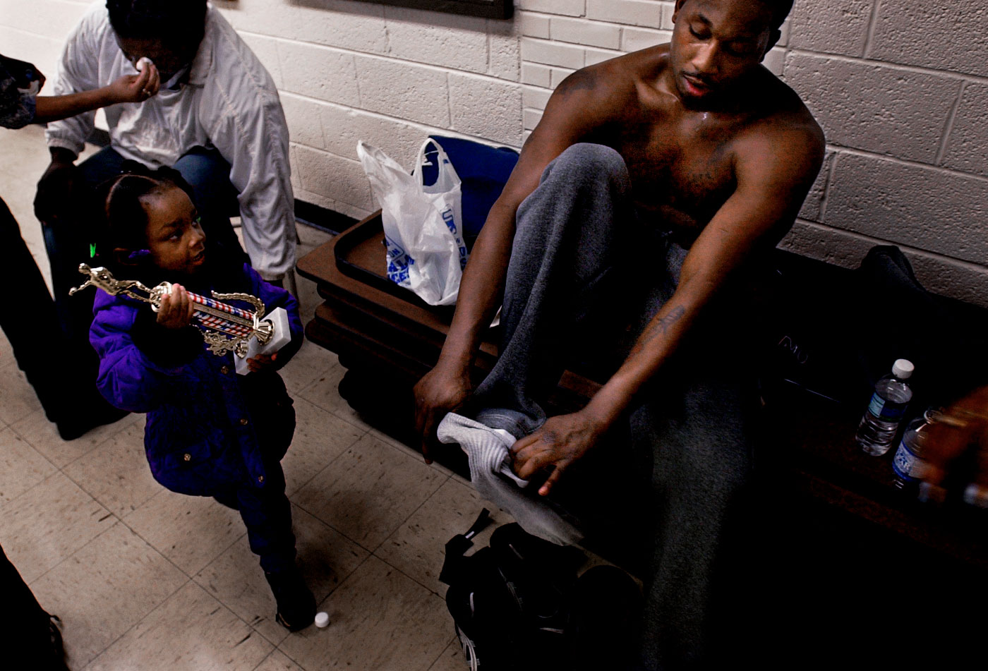 Darnelle Hobson looks up to her father, James Hobson, who won the heavyweight division on Saturday night, the final night of the competition. At left is the man he beat for the championship.