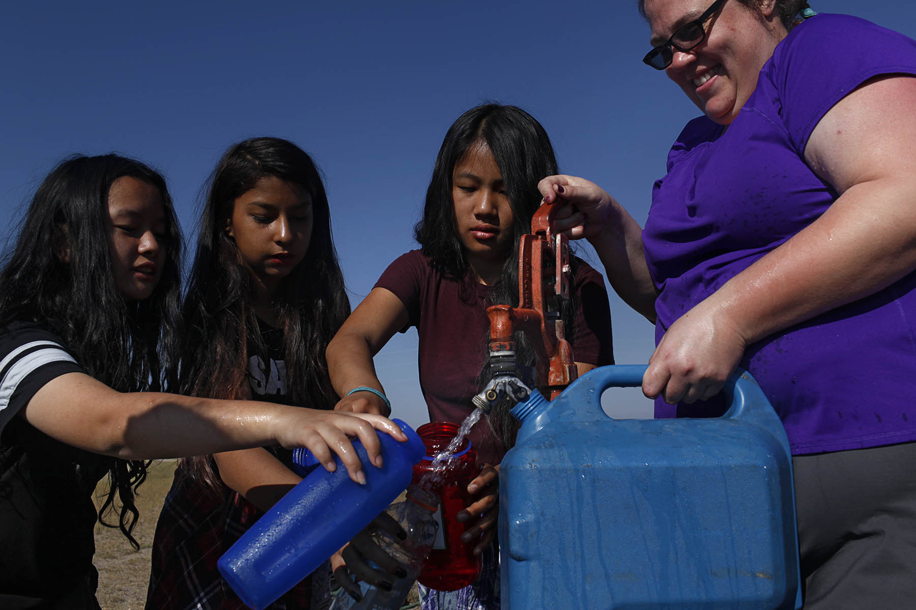(l-r) Sumina Magar, 14, Sostika Chhetri, 14, Dechen Drukpa, 14, and Jamie Stanley, 33, gather water before making dinner at their campsite in Hooper, Colo. on Sept. 3, 2017. Stanley is the Venturing Crew advisor and is from Denver.