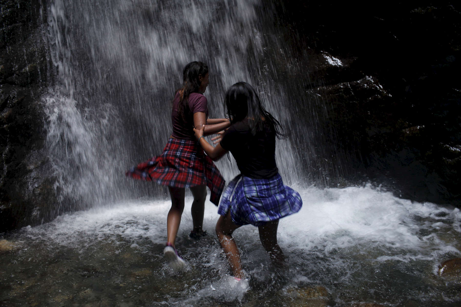 Sostika Chhetri, 14, left, and Dechen Drukpa, 14, run into the Zapata Falls on Sept. 3, 2017. The falls are not far from the Great Sand Dunes National Park and Preserve, where the girls spent much of the day.