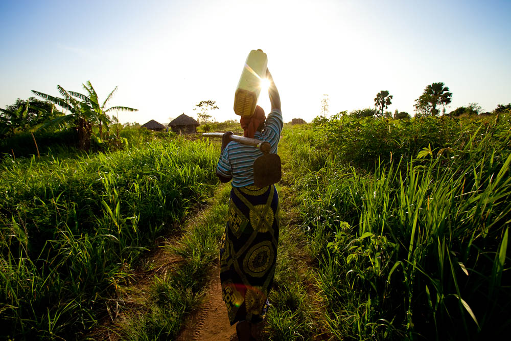 Manjeri, 55, walks to her farm north of Gulu, Uganda.