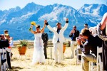 A newly wedded couple raise their hands in celebration just moments after their first kiss as husband and wife in front of the Sawtooth Mountains of Stanley, Idaho.