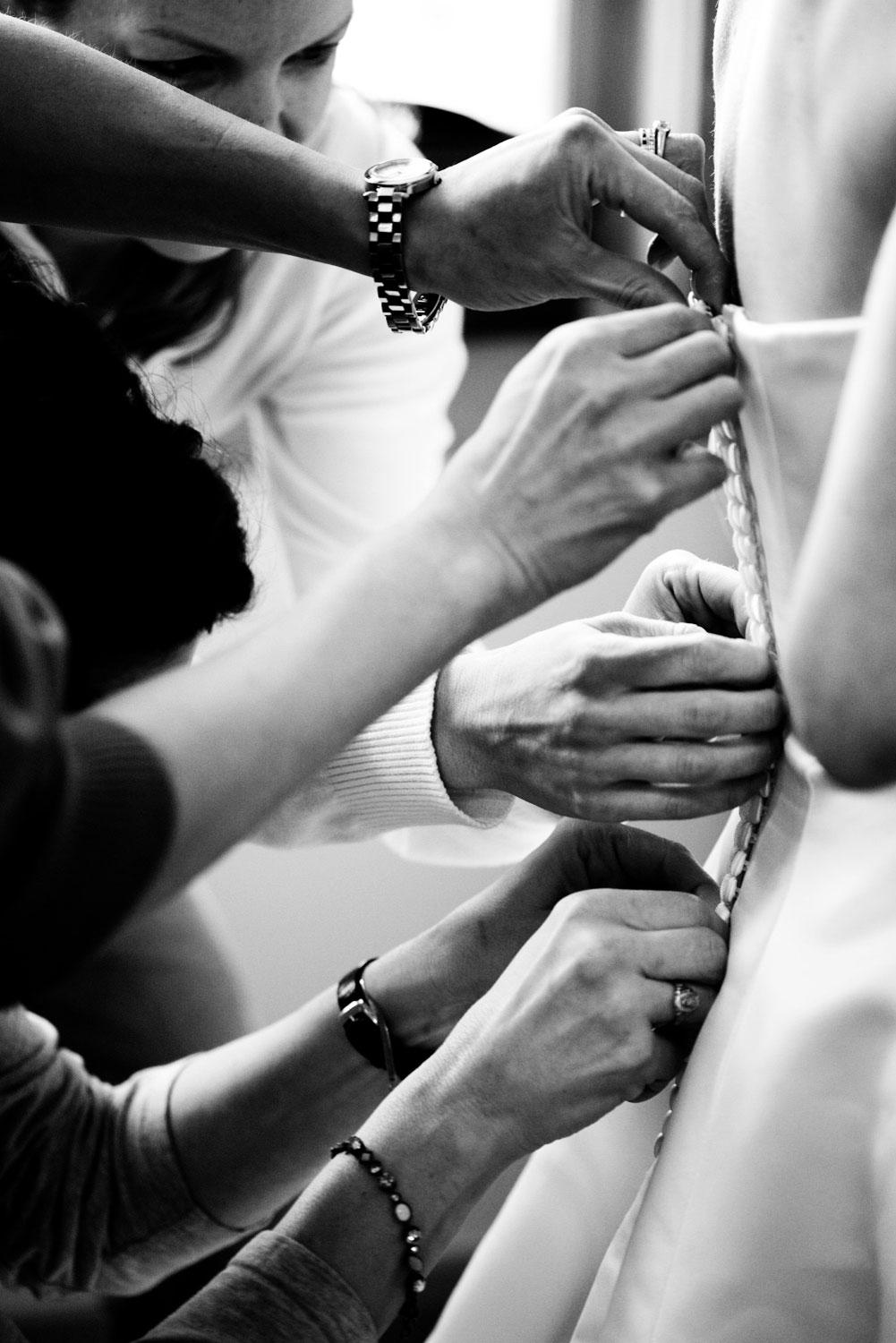 A photograph showing the many hands it takes to button a Bride's wedding dress!