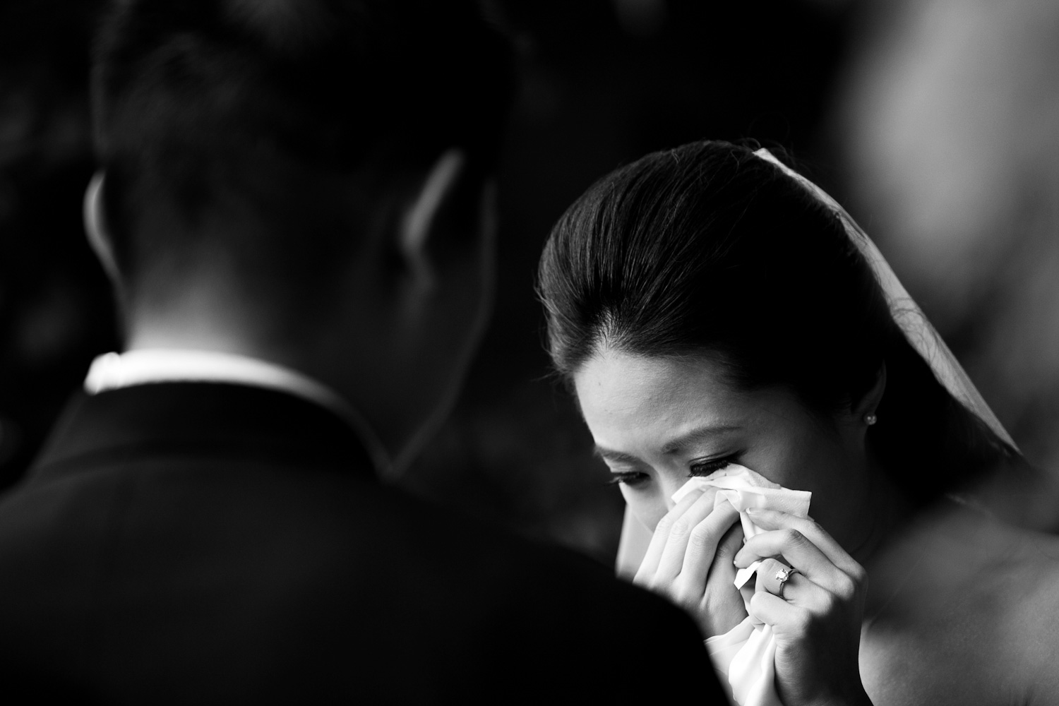 An emotional bride wipes a tear from her eye during her wedding at Wine and Roses in Lodi, California.