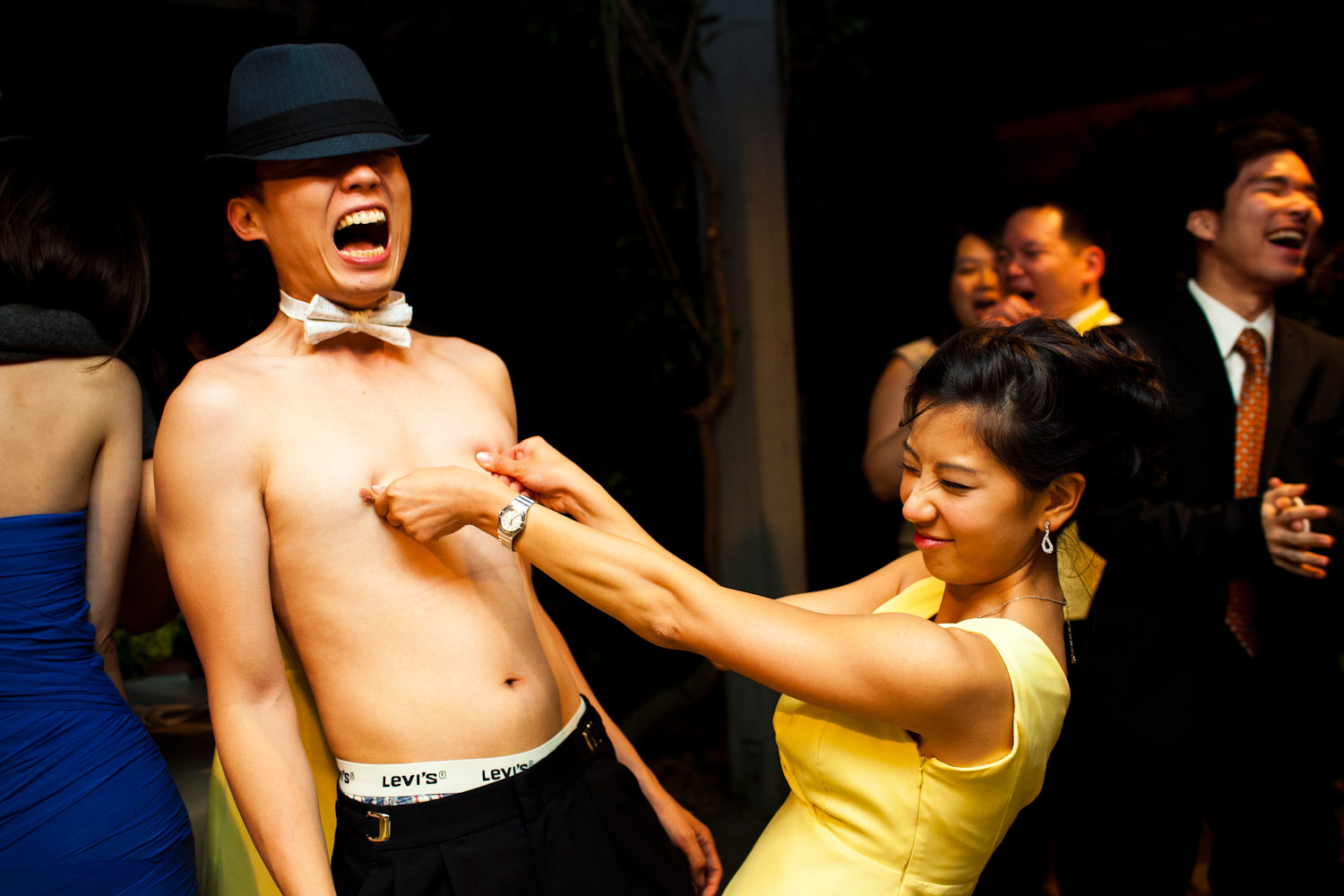 A bridesmaid gives a groomsman a titty-twister during the reception party at Wine and Roses in Lodi, California.