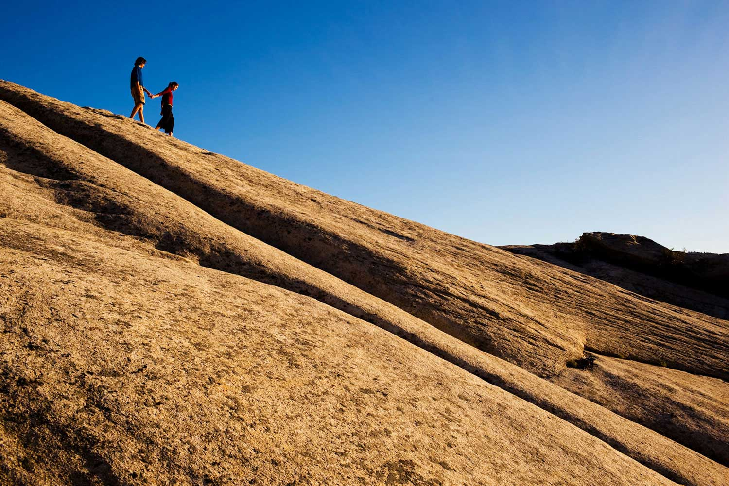 A couple walks down a granit slope at the City of Rocks National Monument, Idaho.