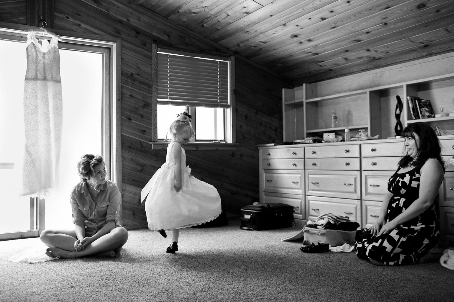 A flower girl tests her dress out with a twirl while the bride and her mother watch.