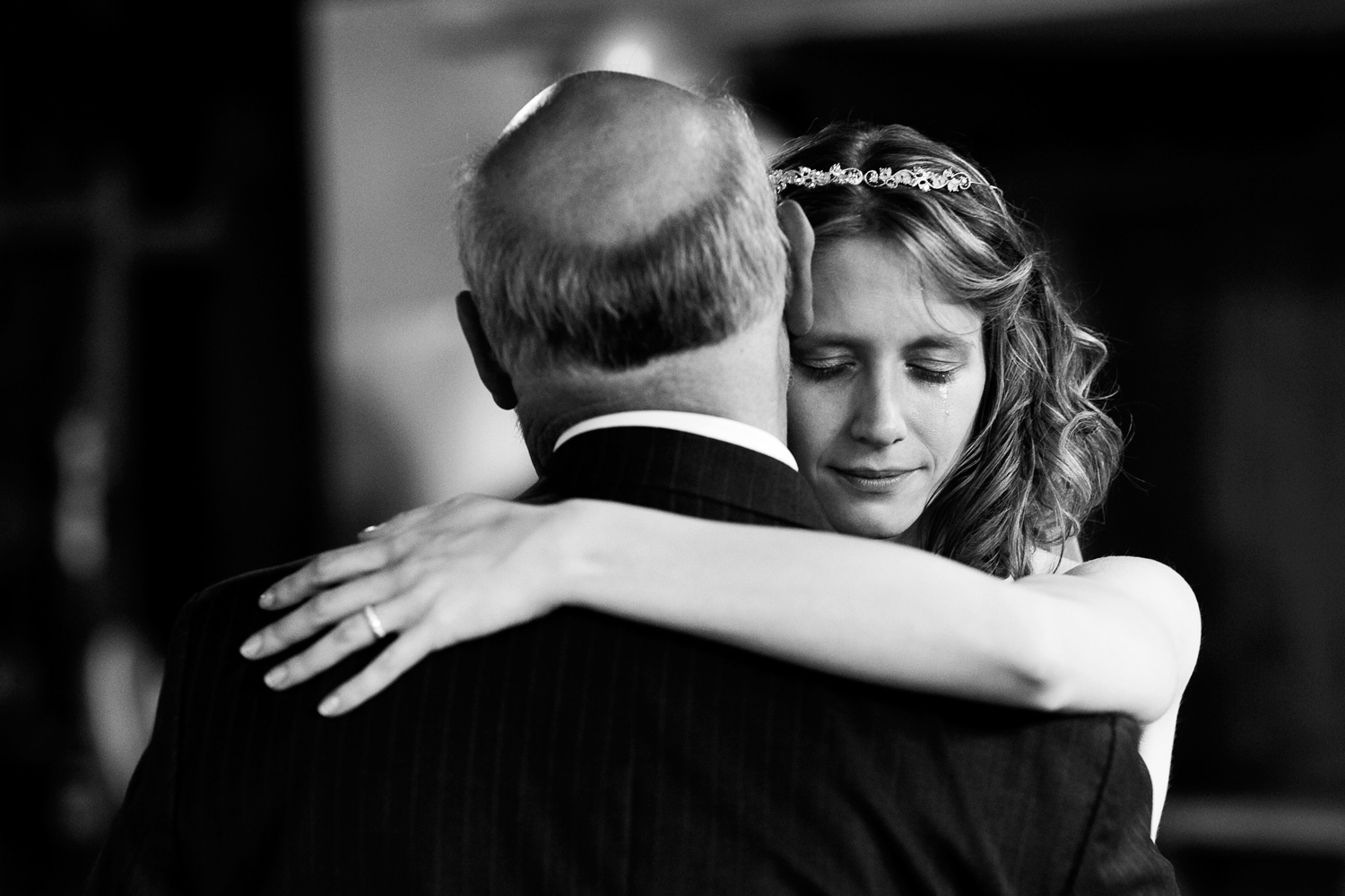 A bride sheds a tear during her father-daughter dance.